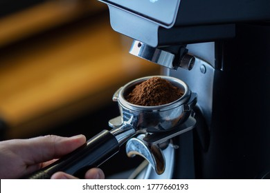 coffee grinder grinding coffee pouring into a portafilter