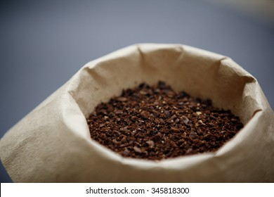 Coffee Grounds in a Brown Paper Filter with Grey Background