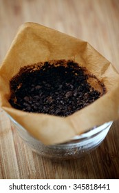 Coffee Grounds in a Paper Filter in a Glass Bowl with a Wooden Background