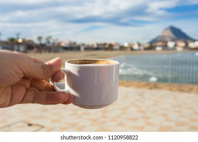 Сup of coffee in hand on the background of a beautiful beach