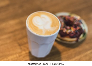 coffee with a heart made of milk and a donut on a wooden table. Bad breakfast. Coffee with a drawn heart and milk on a wooden table in a coffee shop. chocolate donut with scattering on the table next
