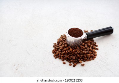 Coffee holder placed into coffee roasted beans on the white table in daylight