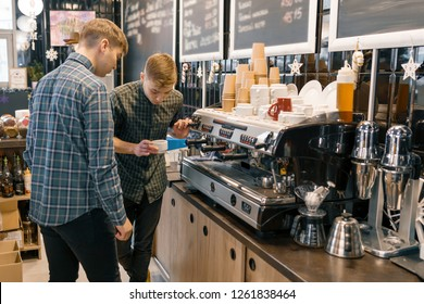 Coffee house, small business, male barista near the coffee machine. Experienced barista coaching teaching young man to brew coffee in professional coffee machine.