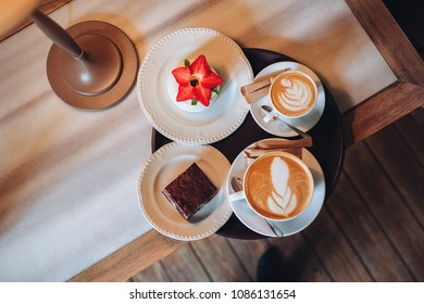 Coffee house. Two cups on a wooden table. Coffee for a couple. Dessert. Brownie, cheesecake. Cappuccino, latte, foam.