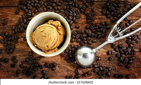 Coffee ice cream decorated with coffee beans on rustic wooden table. High contrast and toned image.