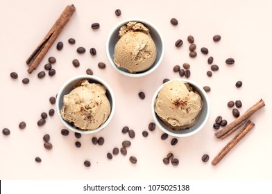 Coffee ice cream on pink pastel background, top view. Frozen coffee gelato ice cream with coffee beans and cinnamon - healthy summer dessert.