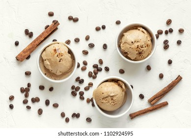 Coffee ice cream on white background, top view. Frozen coffee gelato ice cream with coffee beans and cinnamon - healthy summer dessert.