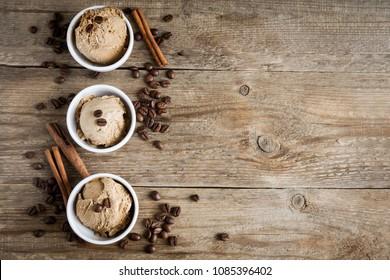 Coffee ice cream on wooden background. Homemade coffee gelato ice cream with coffee beans - healthy summer vegan dessert.