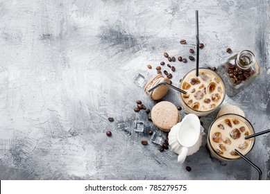 coffee ice in glass, macaroons,, pieces of chocolate and coffee beans  on a gray  table , top view, copy space