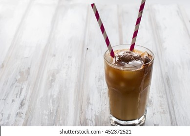 coffee with ice in a glass on a dark wooden table