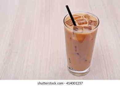Coffee with ice on light wooden background