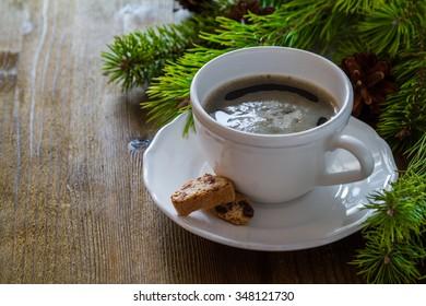 Coffee and italian cookies biscotti, christmas tree, rustic wood background