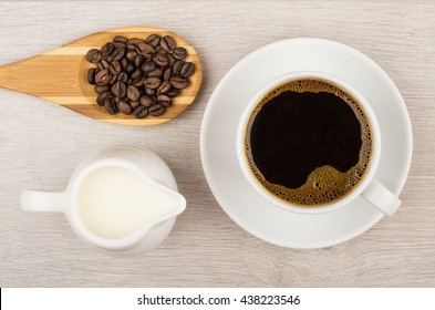 Coffee, jug milk and wooden spoon with coffee beans on table. Top view