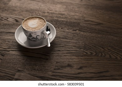 Coffee latte art. A cup of espresso served on a dark wooden table with empty copy space