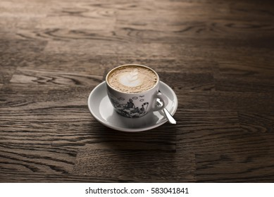 Coffee latte art. A cup of espresso on a dark wooden table