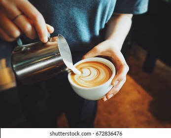 coffee latte art make by women barista in coffee shop cafe vintage color tone .with copy space