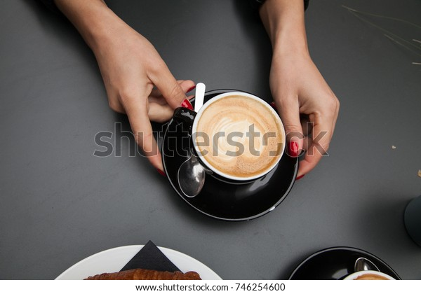 Coffee latte art on woman hand in coffee shop in vintage color filter