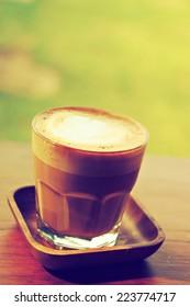 Coffee latte art on the wood vintage desk in vintage color tone