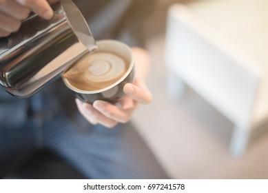 coffee latte art in coffee shop vintage color tone blur