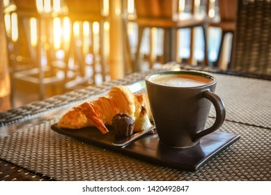 Coffee latte with croissant and pastry on table in cafe closeup
