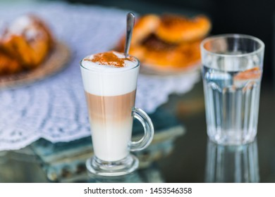 Coffee latte in glass with milk foam and cocoa, cinnamon powder and cake bisquit for breakfast