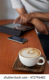 coffee latte on the wood desk with a man use tablet background