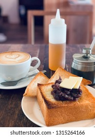 Coffee latte and toast bread with butter and japanese red bean at cafe.