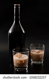 Coffee liqueur and alcoholic beverages based on milk and whiskey concept with Irish cream bottle and glasses with ice isolated on dark black background