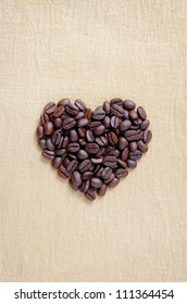 coffee lover sign, Pile of brown coffee beans in heart shape, close up of coffee beans in love symbol on sack cloth
