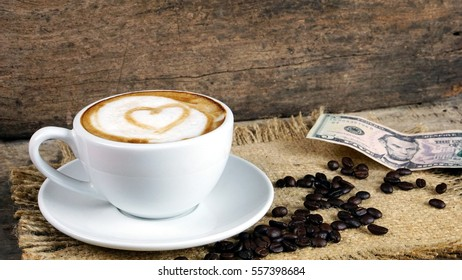 Coffee Lovers. A cup of latte, cappuccino or espresso coffee with milk put on a wood table with dark roasted coffee beans and 5 Dollars. Drawing the hearts on the milk to be in love on Valentine's day