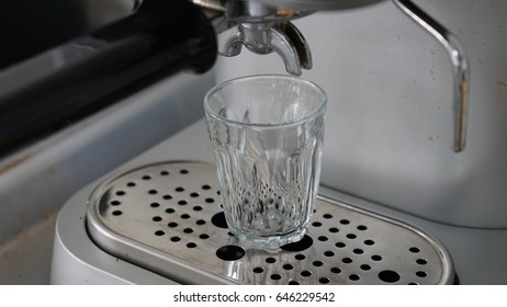 The coffee machine with the bucket holding, ready for espresso stream into the glass shot which standby on the grill, metal and steel equipment