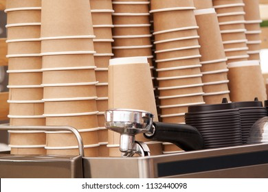 coffee machine in a cafe with stacks of paper cups from kraft paper for coffee preparation with you