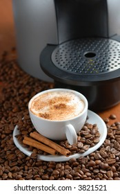 Coffee machine and cup of cappuccino with cinnamon. Spilled out coffee beans.