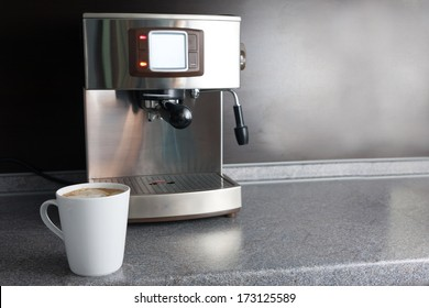 Coffee machine and freshly made cup of latte of table