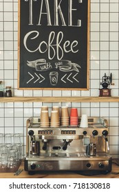 coffee machine, glassware and paper cups in coffee shop