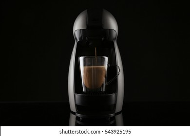Coffee machine pouring espresso into cup on black background