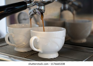 Coffee machine in the process of pouring coffee expresso into 2 white cups