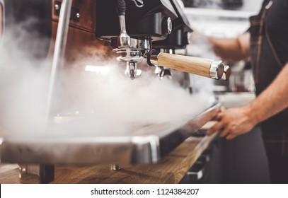 Coffee machine in steam, barista preparing coffee at cafe