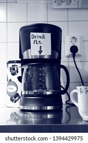"""A coffee machine in working mode has a written note stuck on it above the carafe saying """"Drink me"""" with an arrow pointing down at the carafe"""