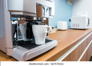 Coffee maker with coffee cup.