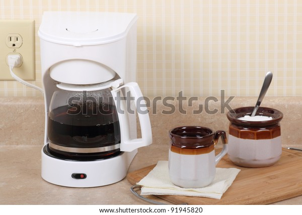 Coffee maker, cup of coffee and sugar bowl on a kitchen counter