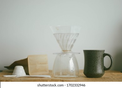 coffee maker equipment for pour over method: pour over brewer, filter paper, mug, measurement spoon and fresh ground coffee