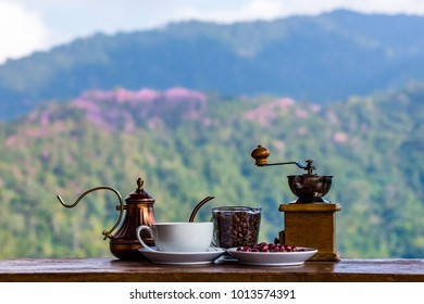 Coffee Maker Includes  grinder, pot with coffee cup on  a mountainous background.