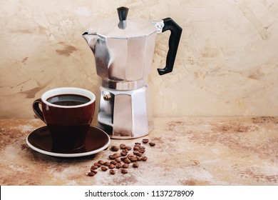 Coffee maker moka pot and a cup of coffee with roasted coffee beans. Space for text, horizontal