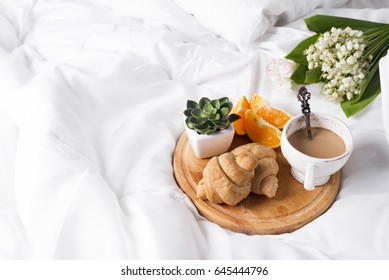 Coffee with milk and a bouquet of lilies of the valley in bed with a croissant and an orange. a place for the text