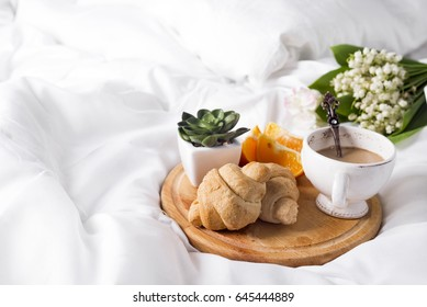Coffee with milk and a bouquet of lilies of the valley in bed with a croissant and an orange. Breakfast in bed Morning, a place for the text