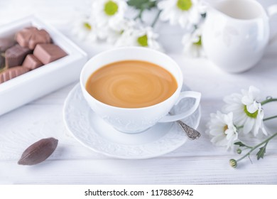 Coffee with milk, chokolate candies and chrysanthemums flowers on a white wooden background