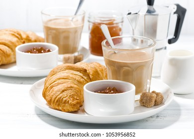 coffee with milk and croissants with jam for breakfast, closeup, horizontal