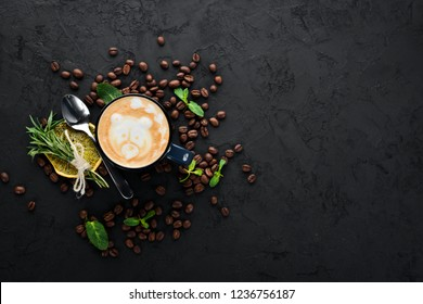 Coffee with milk in a cup. Cappuccino. On a black stone background. Top view. Free copy space.