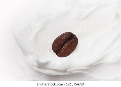 Coffee milk dessert. Coffee beans among yogurt or milk. Close up. Coffee bean on the background of a splash of cream